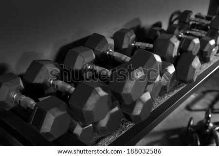 Dumbbells and Kettlebells weight training equipment at gym - stock photo