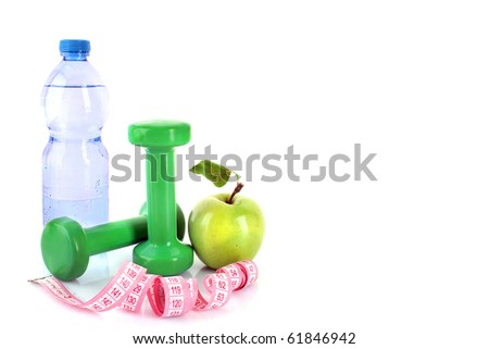 Dumbbells, green apple, measuring tape and a bottle of water isolaeted on white - stock photo