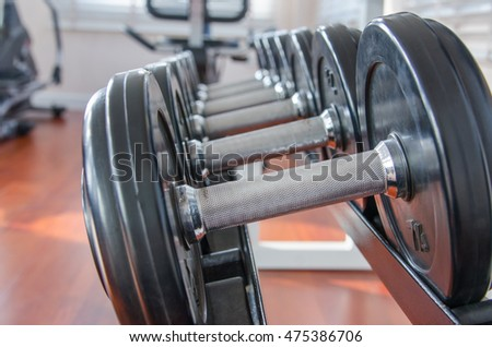 Dumbbells in a row on a rack, fitness in the sport club.