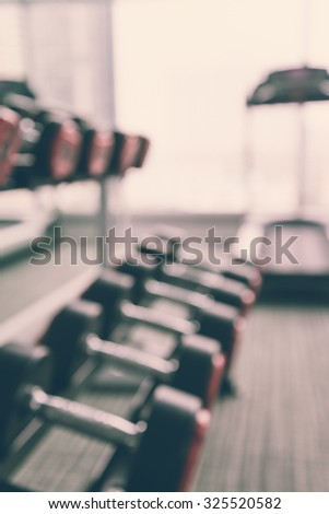 Dumbbells in modern luxury fitness center abstract blur background