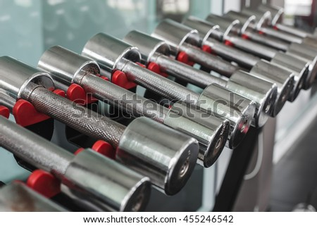 Dumbbells in modern sports club. Weight training equipment - stock photo