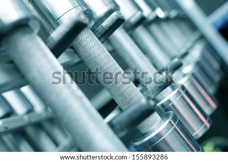 dumbbells lie on a rack in a gym - stock photo