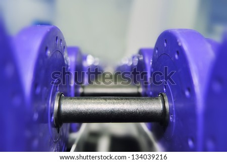 Dumbbells of different scales lie on the sports shelf - stock photo