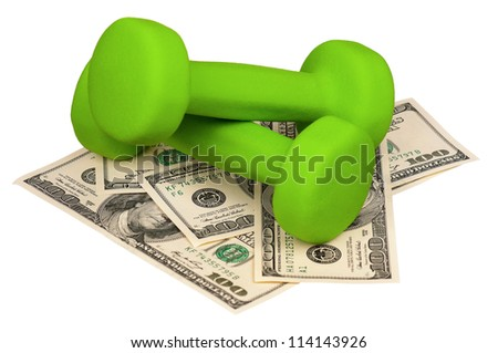 Dumbbells on heap of dollars isolated on a white background - stock photo