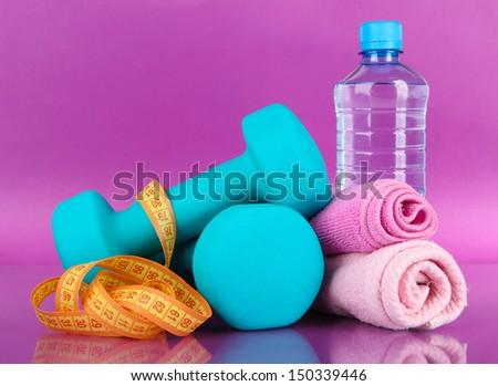 Dumbbells on purple background - stock photo