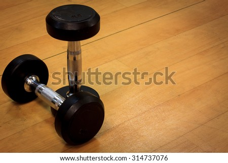 Dumbbells on the wood background and vignetting. - stock photo