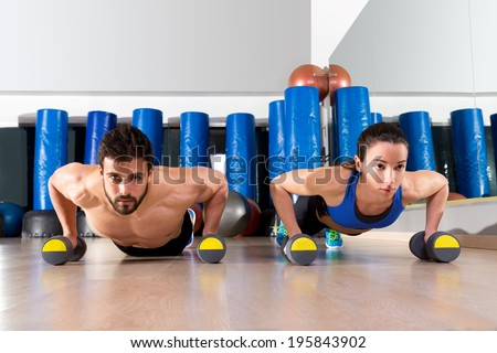 Dumbbells push-ups pushups couple at fitness gym workout - stock photo