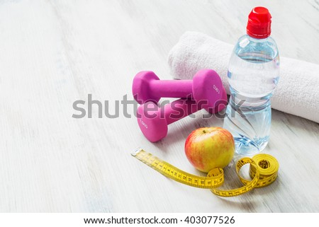 Dumbbells, water, towel, apple, and tape measure