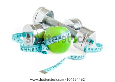 Dumbbells with an apple on a white background. A healthy way of life - stock photo