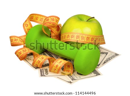 Dumbbells with apple and measure tape on heap of dollars isolated on a white background - stock photo