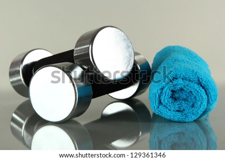 Dumbbells with towel on grey background - stock photo