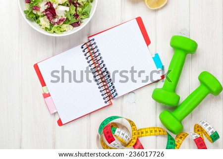 Dumbells, tape measure, healthy food and notepad for copy space. Fitness and health - stock photo
