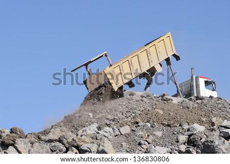 Dump truck dumper lorry dumping load - stock photo