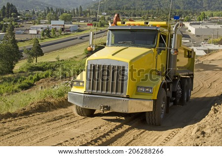 dump truck moving rock and dirt at a new commercial construction development project - stock photo