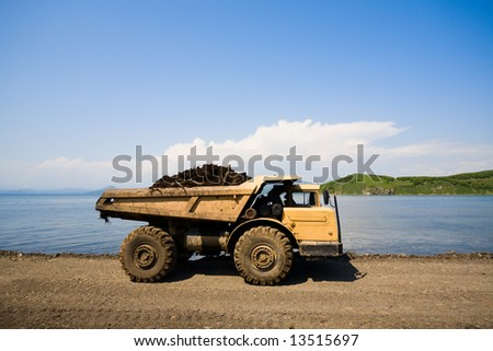 dump truck on a background of the sea - stock photo