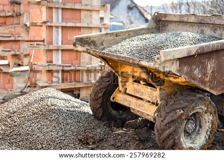Dumper truck unloading construction gravel, sand and crushed stones - stock photo