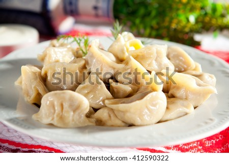 Dumplings Garnished withSour Cream, Butter and Dill - stock photo