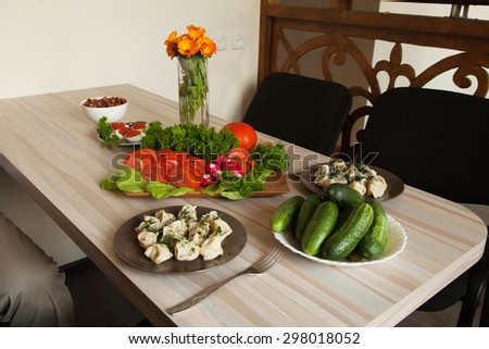 dumplings, vegetables and greens on a plate standing on the table - stock photo