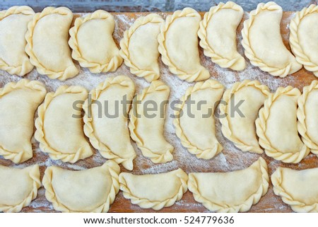 Dumplings with potatoes on the kitchen board. Dumplings with potatoes (or cottage cheese, cabbage, cherries, etc.) is a traditional Ukrainian dish is also known as Varenyky or Vareniks