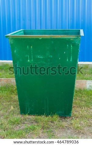 Dumpster standing on the grass against the background of the fence