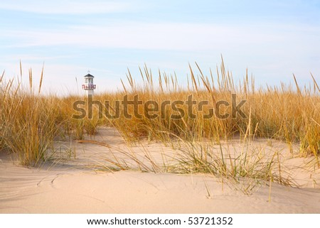 Dune grass and lighthouse in the distance - stock photo
