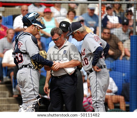 DUNEDIN - MARCH 22: An Tigers trainer looks at catcher Max St. Pierre (l) manager Jim Leyland (r) also looking on. St. Pierre was injured in the March 22, 2010 spring training game in Dunedin, FL