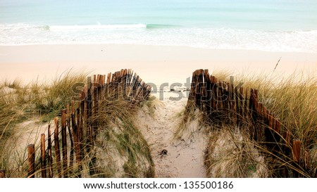 Dunes, Fences and ocean shore on a sandy beach - stock photo