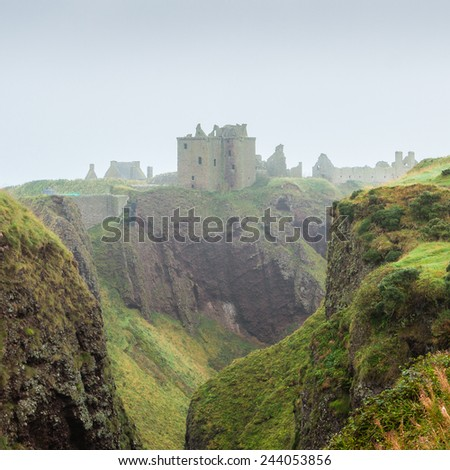 Dunnottar castle, Stonehaven, Aberdeen, Scotland. Evocative fortress ruins shrouded in mist and flanked by scarped rocky formations. This landmark's history spans since the Picts until today - stock photo