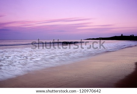 Dunstaburgh Castle at sunset from the beach - stock photo