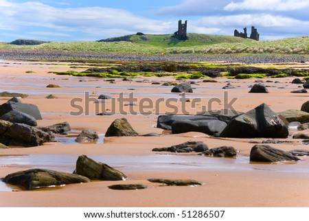 Dunstanburgh Castle seen from Embleston beach - stock photo