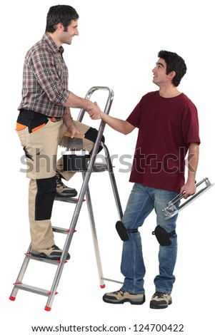 duo of craftsmen shaking hands - stock photo