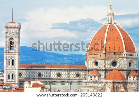 Duomo of Florence with the Giotto Beltower over sky with clouds - stock photo