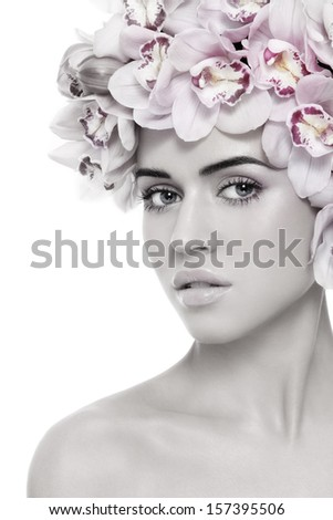 Duotone portrait of young beautiful tanned sexy woman with fresh make-up and orchids in her hair, on white background