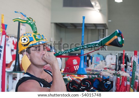 DURBAN - MAY 04: Vuvuzela is the trumpet of south african soccer fans.  A brazilian is showing how to sing it at the durban new stadium, may 04 2010 in Durban, SouthAfrica - stock photo