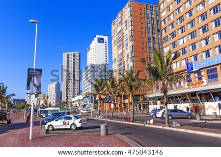 DURBAN, SOUTH AFRICA - AUGUST 25, 2016: Many early morning unknown people on on palm tree lined Esplanade against city Skyline on Golden Mile Beach front in Durban, South Africa