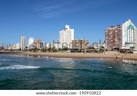DURBAN, SOUTH AFRICA - MAY 3, 2014: View of people and ocean on North beach against Durban City Skyline in South Africa