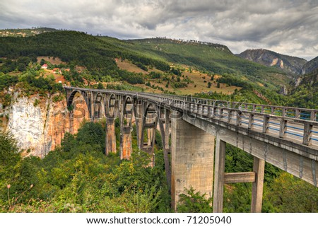 Durdevica arched Tara Bridge over green Tara Canyon. One of the world deepest Canyons and UNESCO World Heritage, Montenegro. - stock photo