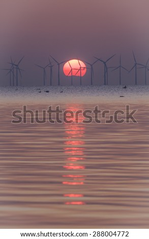 During the sunset, the sun, itsself a natural power, putting focus on other natural power, the wind. Two global and natural power system in one image. From Oresund, between Denmark and Sweden. - stock photo