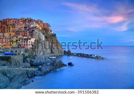 Dusk light illuminates the sky and historical buildings of Manarola, Cinque Terre, Italy - stock photo