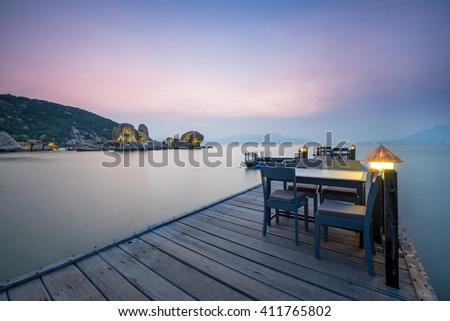 Dusk over a beautiful, clean and fresh beach with rock and mountain around. Awesome place for holidays. Tables and chairs are placed on jetty for customers enjoy and relax. - stock photo
