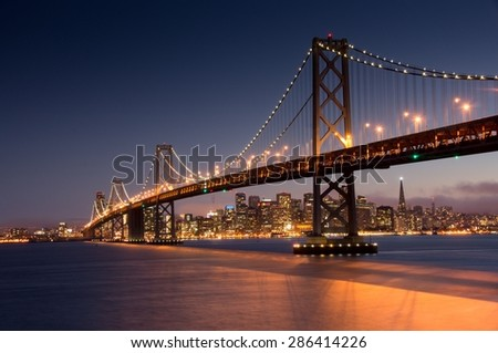 Dusk over San Francisco Bay Bridge and Skyline from Yerba Buena Island - stock photo