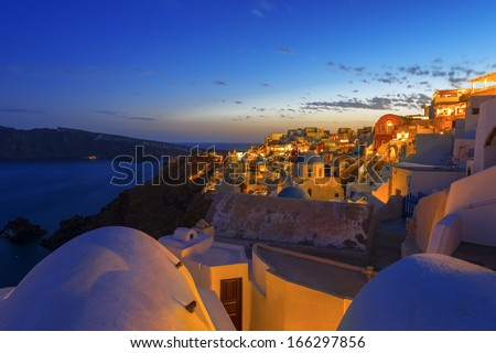 Dusk overlooking buildings on the Caldera at Oia Santorini Greece Europe at night with sea background - stock photo