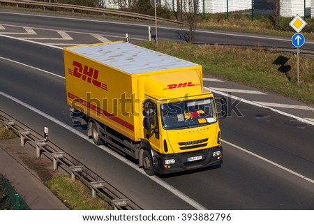 DUSSELDORF,GERMANY - FEBRUARY 16,2016 DHL delivery truck on the highway. DHL is a world wide courier company that operates in 220 countries with over 285,000 employees - stock photo