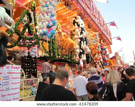 DUSSELDORF, GERMANY - JULY 24: Visitors at Lottery Stall at Kirmes on July 24, 2010 in Dusseldorf, Germany. Kirmes is the biggest summer fair on the north Rhein in Germany. - stock photo