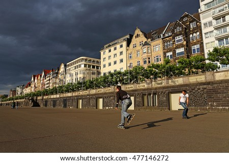 DUSSELDORF, GERMANY - MAY 26: Athletes rollerblading on street in front of the building near the Rhine river on May 26, 2011 in Dusseldorf, Germany. The Embankment of Rhine river in Dusseldorf