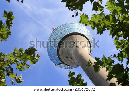 Dusseldorf rhine tower framed by trees. The rhine tower is located in the trendy Dusseldorf media harbor district next to the river rhine. - stock photo