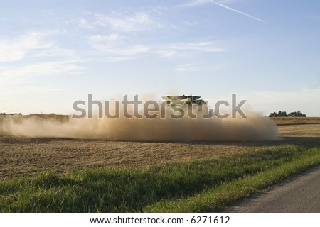 dust from a combine fills the air - stock photo