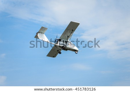 Duster, small old plane for agricultural spraying, flying in the sky - stock photo