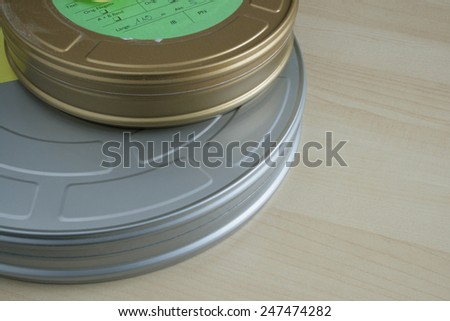 Dusty from storage, a pair of 35mm celluloid film cans on wooden table, one larger silver can and a smaller gold can, complete with a green paper label - stock photo