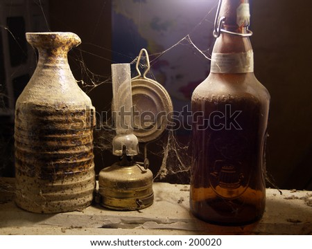 Dusty old bottles and oil lamp - stock photo